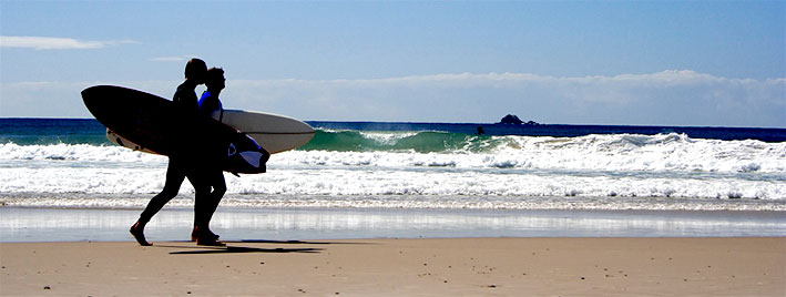 Walking on the beach with surfboards in Biarritz